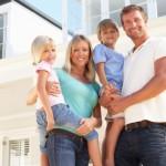 Молодая семья на фоне дома